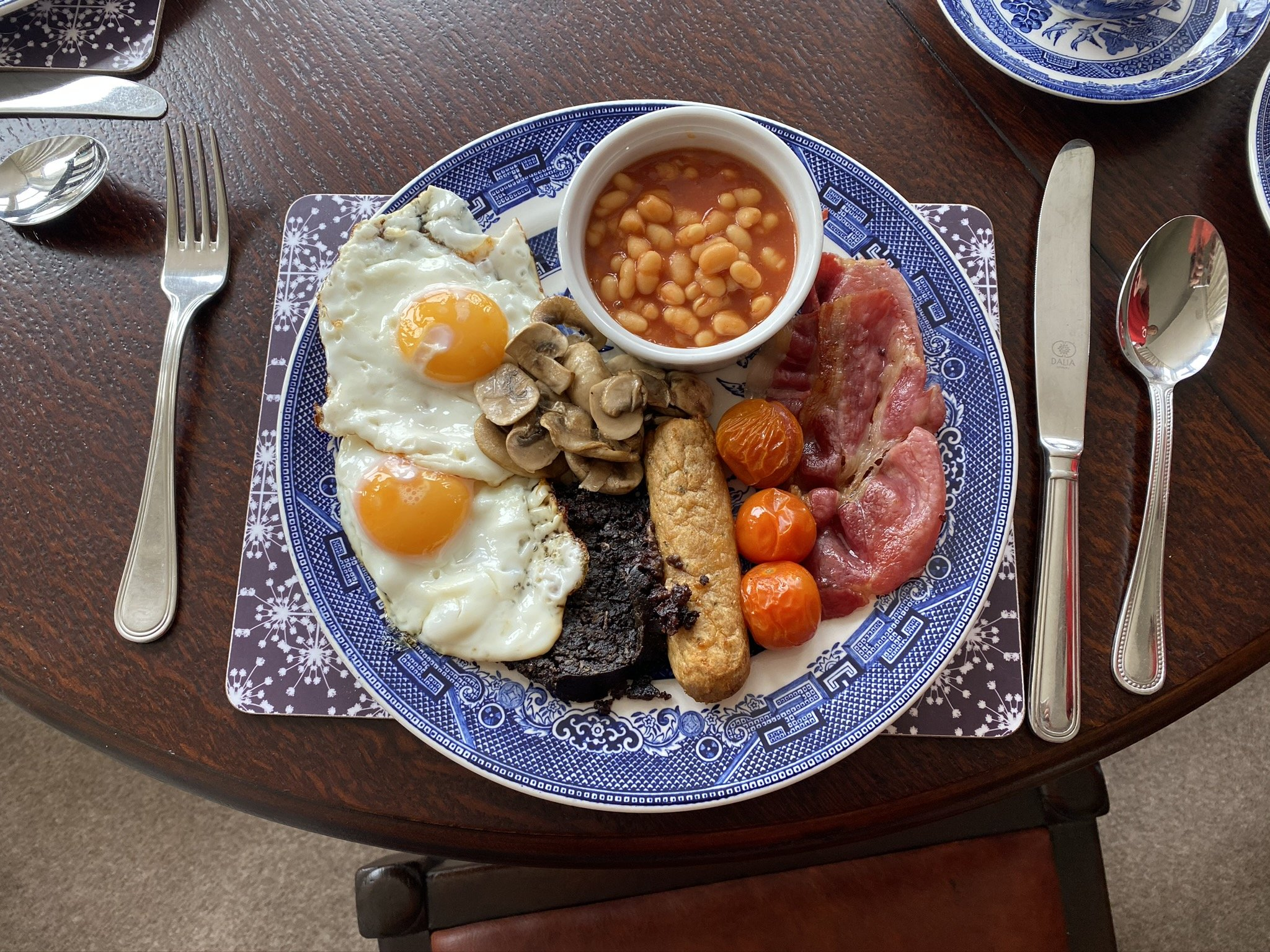 A cooked breakfast of bacon, sausage, muschroom, Skye black pudding, fried egg and baked beans. One of the breakfast options at Millburn Bed and Breakfast