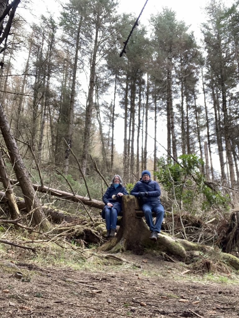 Catriona & Ian sat on a seesaw seat made in a tree stump on one of day walks in Skye
