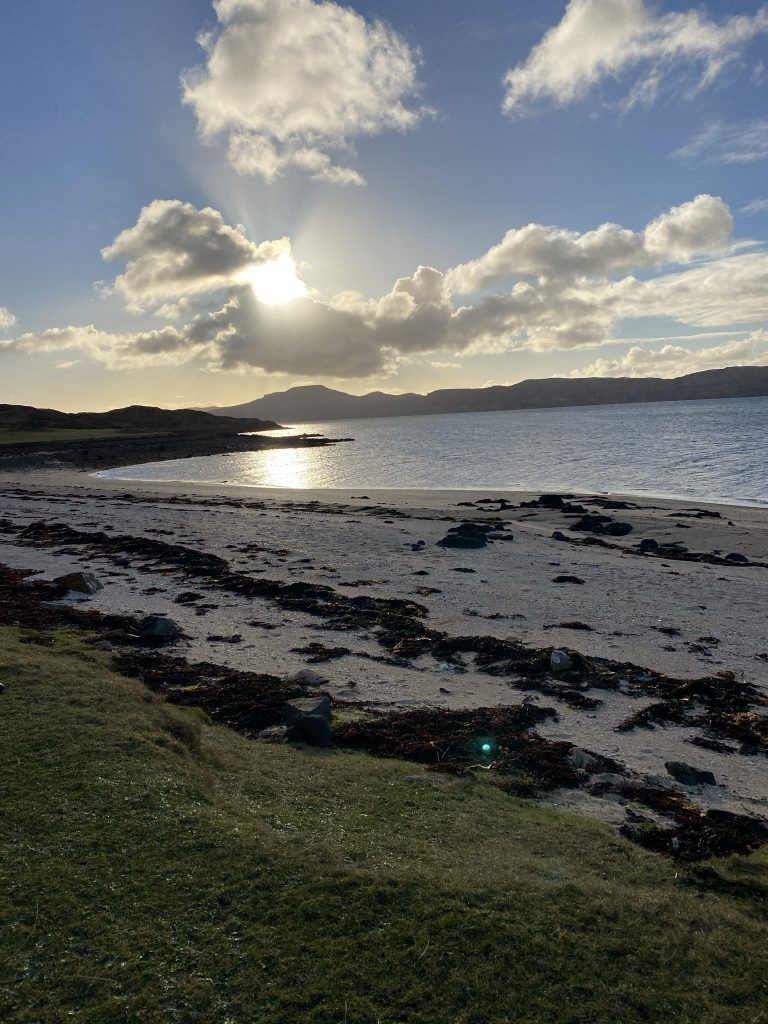 A view from Coral Beach across the loch with sunshine behind the clouds