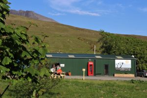 An external view of the cafe at Glenbrittle campsite. A green corrugated building with a red phone box stood outside.
