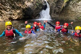 a group of adults and children wearing life vest and helmets. They are in a pool of water below rocks and a waterfall.