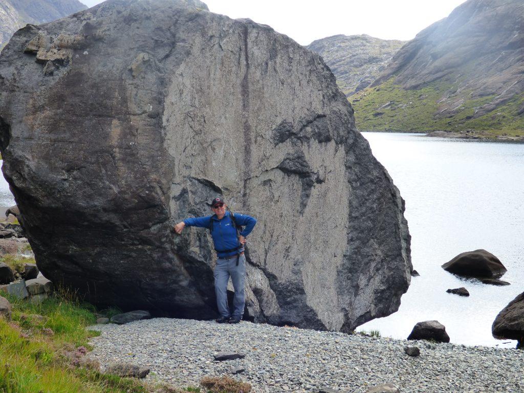 Ian leaning against a huge boulder